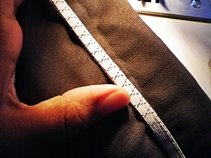The elastic band goes right below the first seam, in between the two sides of the fabric.